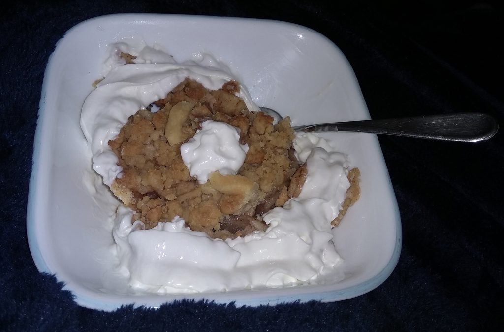 slice of pie with whipped cream in a bowl with spoon